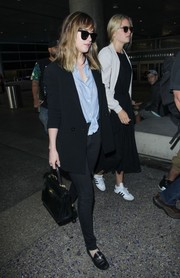 Dakota Johnson caught a flight to LAX wearing a black Chanel blazer teamed with a blue tie-waist button-down and skinny jeans.