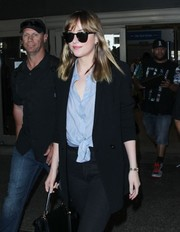 Dakota Johnson hid her eyes behind a pair of Saint Laurent shades while making her way through LAX.