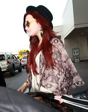 Demi Lovato arrived to catch a flight at LAX wearing a black bowler hat and oversized sunglasses.