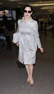 Dita Von Teese added a touch of exotic to her travel attire with snakeskin platforms.