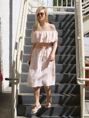 For her footwear, Elle Fanning chose comfy flat sandals with gold accents.