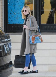 Elle Fanning chose a blue leather shoulder bag with brown patent detailing for her arm candy.