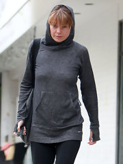 Ellen gets cozy for her workout in a long gray hoodie.