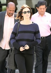 Emily Blunt layered a slouchy blue and black striped sweater over her sleek black travel attire.