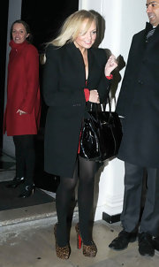 Emma Bunton balanced fierce leopard platforms and a red mini with a sleek black coat.