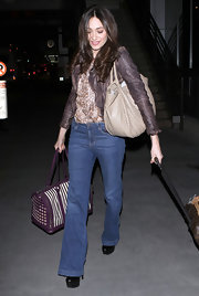 Emmy Rossum made her way through LAX carrying a striped dog carrier with purple leather trim.