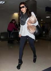 Eva Longoria bundled up at the airport in a loose gray tunic and a complementary charcoal snood.