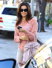 Eva Longoria looked pretty in pink wearing a mesh knit sweater over a white tank.