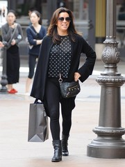 Eva Longoria completed her outfit with a black leather shoulder bag by Balenciaga.