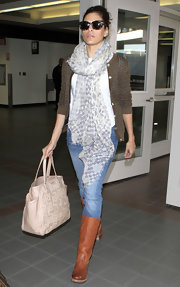 Eva Mendes paired her casual travel attire with cognac knee high boots.