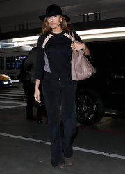 Eva Mendes went casual in wide leg pants while departing on a flight at LAX.