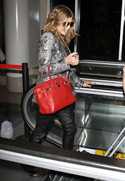 Fergie added bold color to her street attire with a luxe red Hermes Birkin.