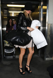Fergie traveled in style, matching her leather jacket to an sleek oversize tote.
