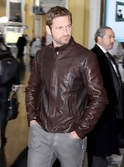 Gerard Butler opted for a cool brown motorcycle jacket for his travel look.
