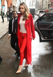 Gigi Hadid turned heads in a chic red trenchcoat by Sally LaPointe while out in New York City.