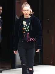 Gigi Hadid kept it youthful in a multi-neon sweatshirt by Versace while out in New York City.