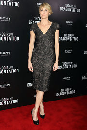 Robin Wright wore a deep-v dress with a metallic sheen for the 'Girl With the Dragon Tatto' NY premiere.