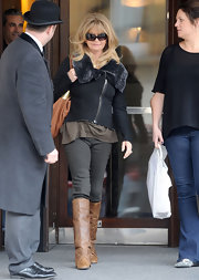 Goldie Hawn looked chic in London in a black fur-trimmed biker coat and knee high boots.
