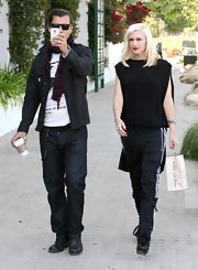 Gwen Stefani paired an elegant black high-low blouse with sports pants for a stroll with hubby Gavin Rossdale.