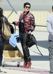 Gwen Stefani went for a sporty travel look with a pink and black tiger-print track jacket.