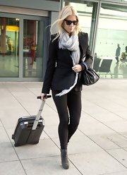 Gwyneth Paltrow traveled in style in a polished black blazer paired with black leggings and a sheer scarf. Gray ankle lace-up boots were the perfect complements to the ultra chic look.