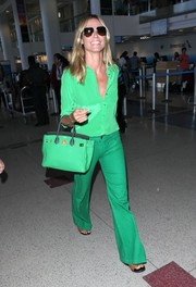 Heidi Klum couldn't be missed in her all-green look while arriving at LAX. Her button-down shirt is by Equipment.