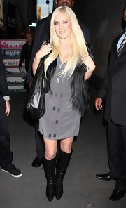 "Heidi wore a dark gray, v-necked ""Rivet Shift Dress""with a pair of knee-high leather boots and a fur vest."