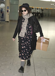 Helena Bonham Carter maintained her signature eclectic style with a ruffled black coat at the airport.