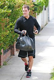 Mike and Hilary made their way to the gym while carrying a travel duffle bag.