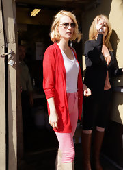 January Jones color-blocked her cute day wear, pairing her pink pants with a red pointelle cardigan.
