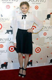 Chloe Moretz channeled an American in Paris in a black knife pleat skirt and a tie neck blouse.
