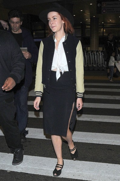 Jena Malone arrived on a flight at LAX wearing a two-tone varsity jacket over a tie-waist button-down.