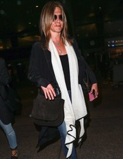 Jennifer Aniston accessorized with a classic black suede bag for a flight to LAX.