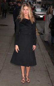 Jennifer wears a darling black coat with an A-line silhouette and large buttons.