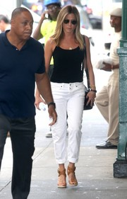 Jennifer Aniston styled her casual look with strappy tan wedges by Burberry.