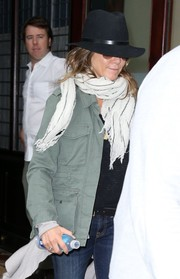 Jennifer Aniston kept cozy with a striped white scarf.