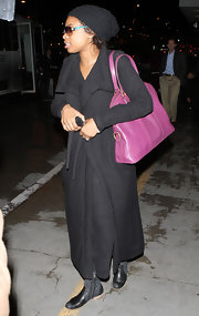 Jennifer Hudson added color to her monochromatic travel attire with a fuchsia leather purse.