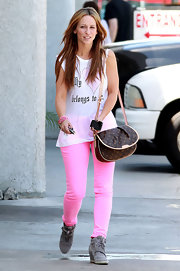 Jennifer Love Hewitt paired her bubblegum pink pants with a gray suede lace-up wedge booties.