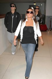 Deena shields her gaze from the paparazzi at LAX in sleek purple tinted sunglasses.