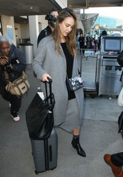 Jessica Alba teamed a gray wool coat with a matching skirt and a black top for a flight to LAX.