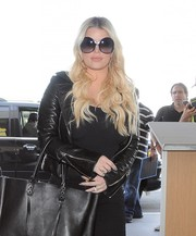 Jessica Simpson caught a flight at LAX wearing her signature oversized shades.