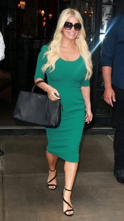 Jessica Simpson displayed her curves in a figure-hugging green Dolce & Gabbana dress while out and about in New York City.