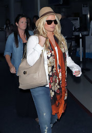 Jessica Simpson teamed her stylish travel wear with a taupe leather hobo bag.