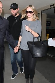 Emily Blunt chose a casual and minimal travel look when she wore this gray top.