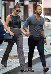 Chrissy Teigen softened her edgy top with a pair of gray silk pants.