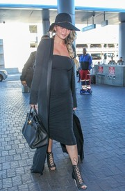 Chrissy Teigen showed off her fierce maternity style with this black evening coat and LBD combo while catching a flight at LAX.