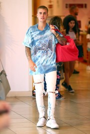 Justin Bieber paired his shirt with ripped white jeans.