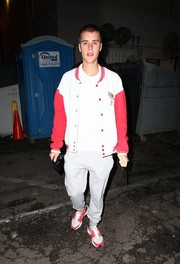 Justin Bieber kept it casual and youthful in a white and red varsity jacket while out in Beverly Hills.