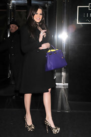Khloe Kardashian hit NYC in Prada Leopard platforms. She paired the catty heels with a purple Hermes bag.