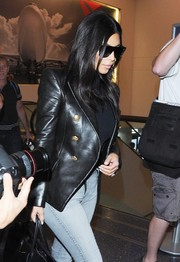 Kim Kardashian brought a dose of edgy glamour to LAX with this bold-shouldered black Balmain leather jacket.